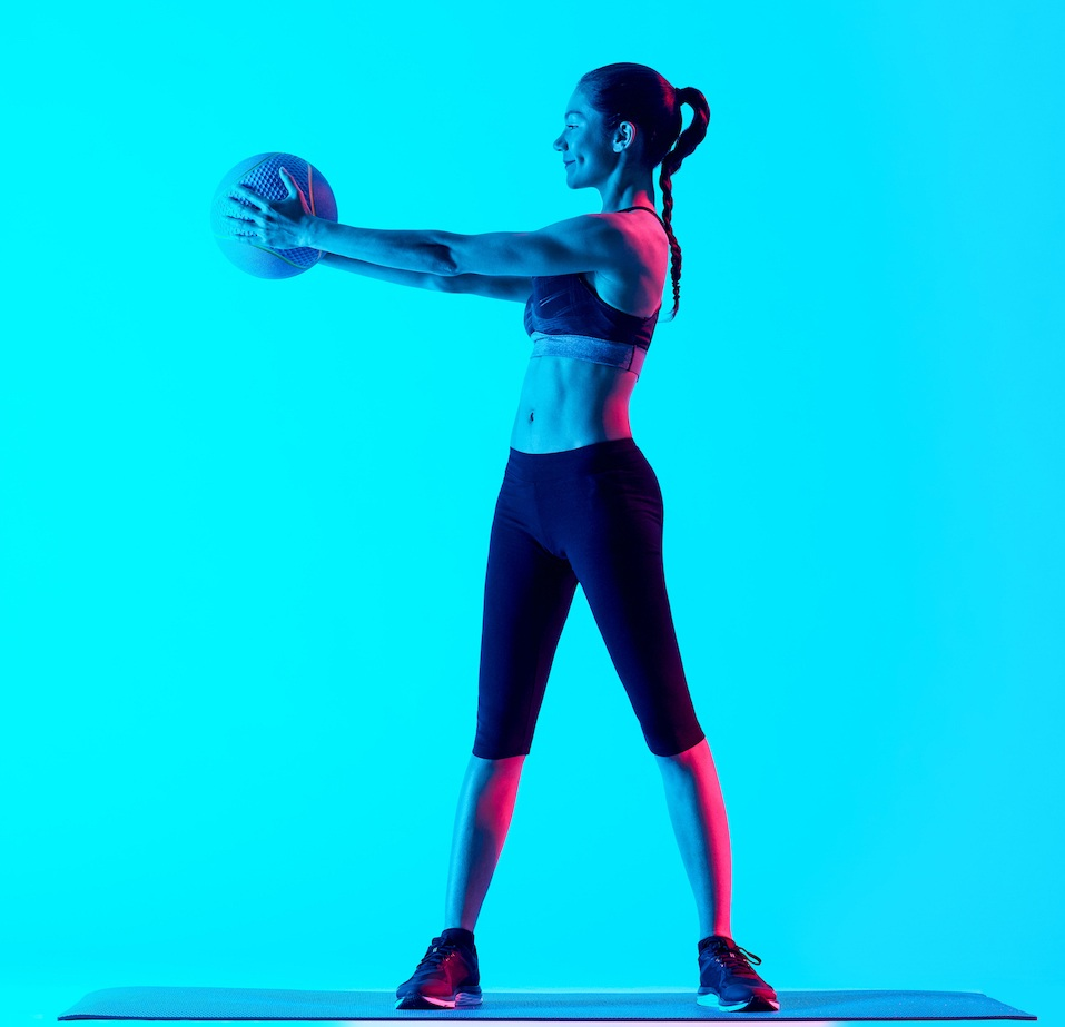 one mixed races woman exercsing Medicine Ball fitness exercices isolated on blue blackground