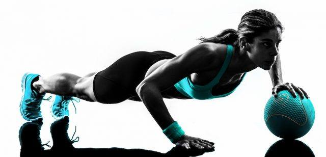 A woman does a workout in blue fitness gear on a white background.
