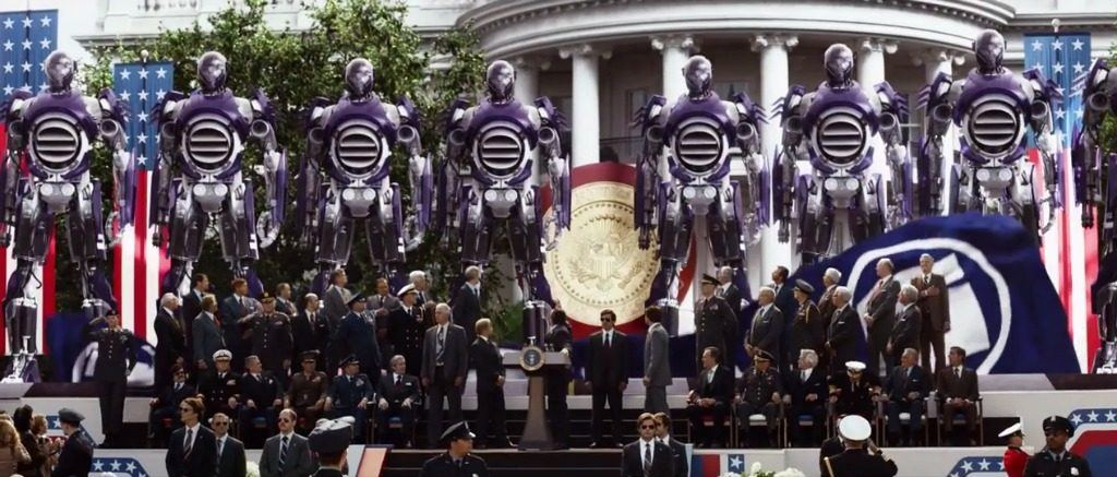 A row of giant robots lined up in front of the White House, surrounded by government officials