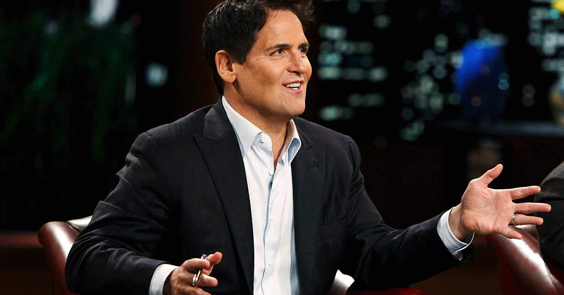 Mark Cuban sits in a chair and holds up his hands on Shark Tank