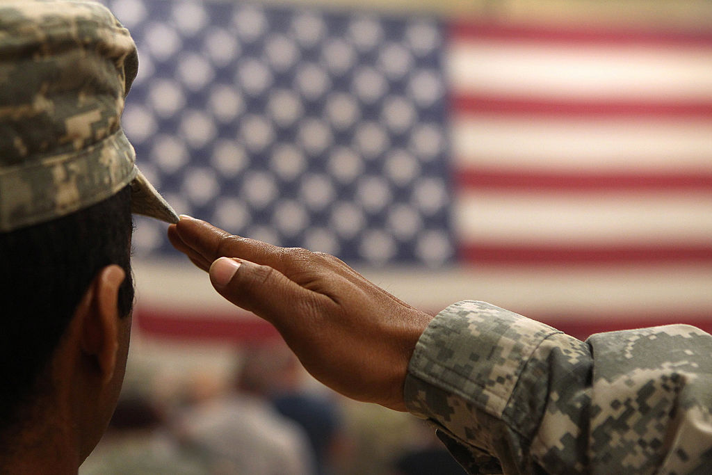 A soldier salutes the flag during a welcome home ceremony
