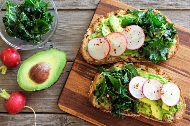 Avocado toast with kale and radish over rustic wood.