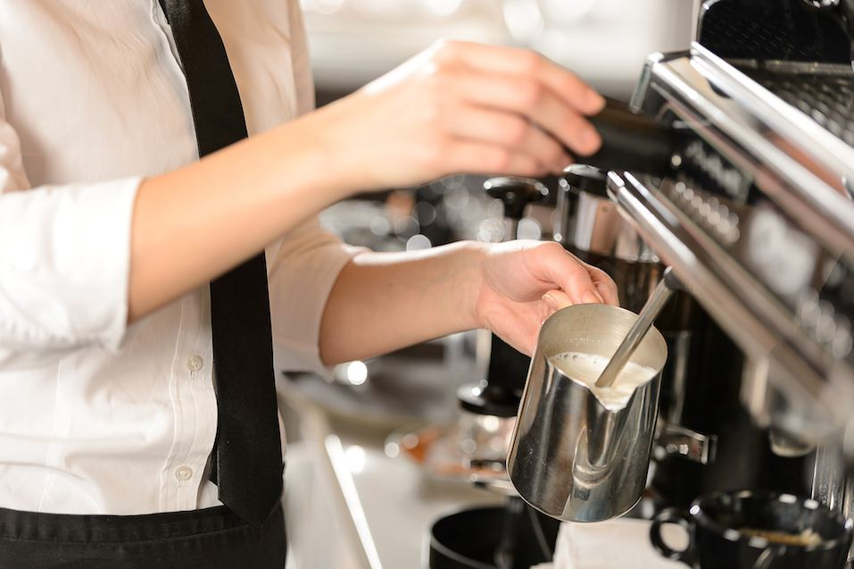 Barista steaming milk for hot cappuccino