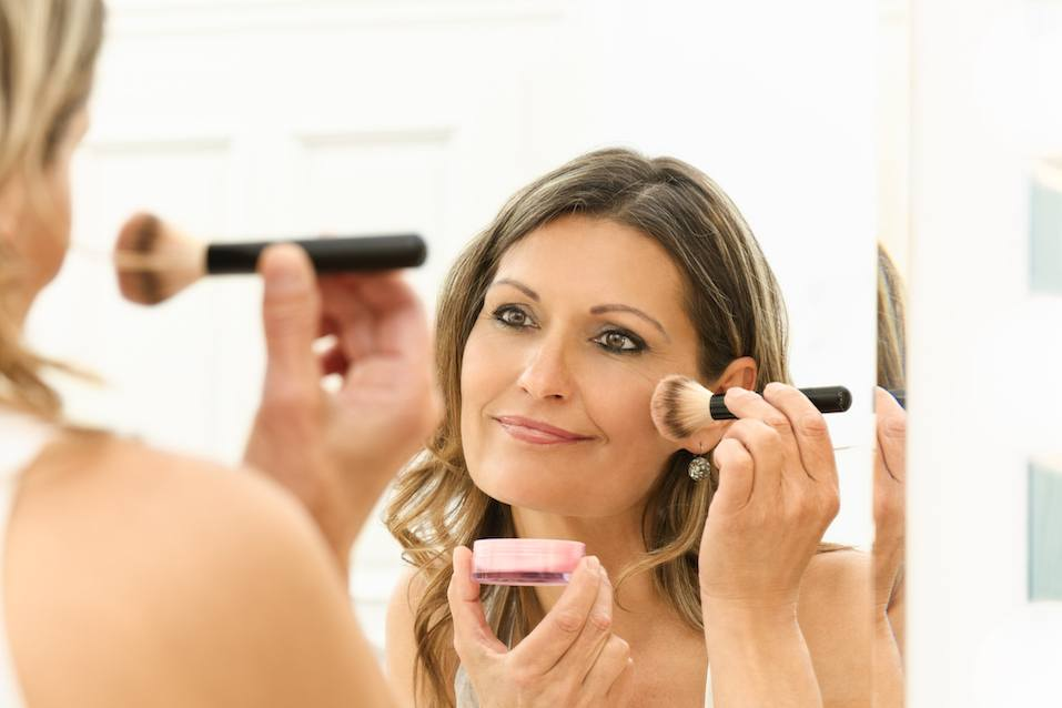 Beautiful 40s woman applying makeup