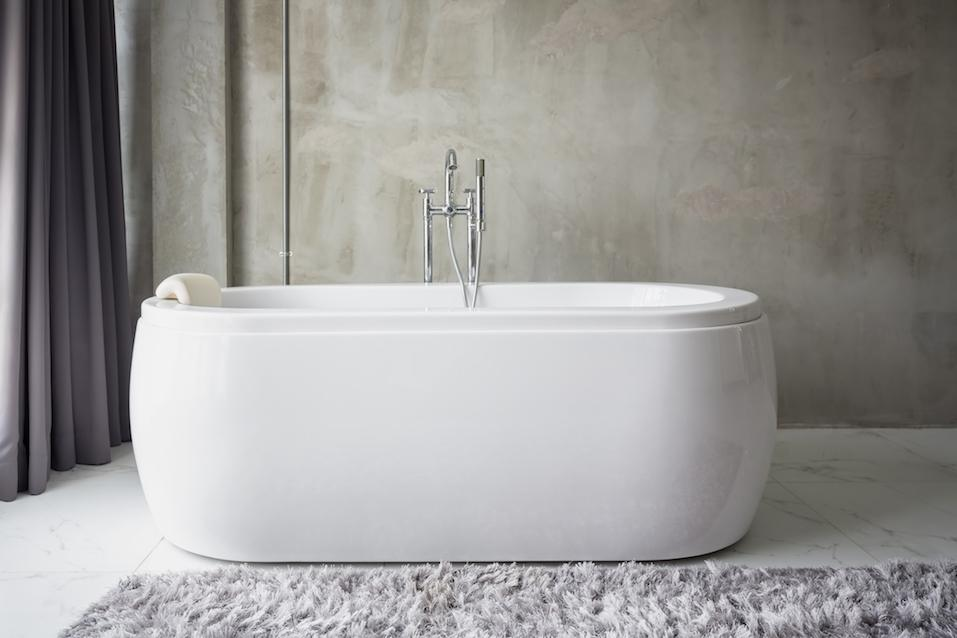Big white bathtub in a middle of minimalist bathroom