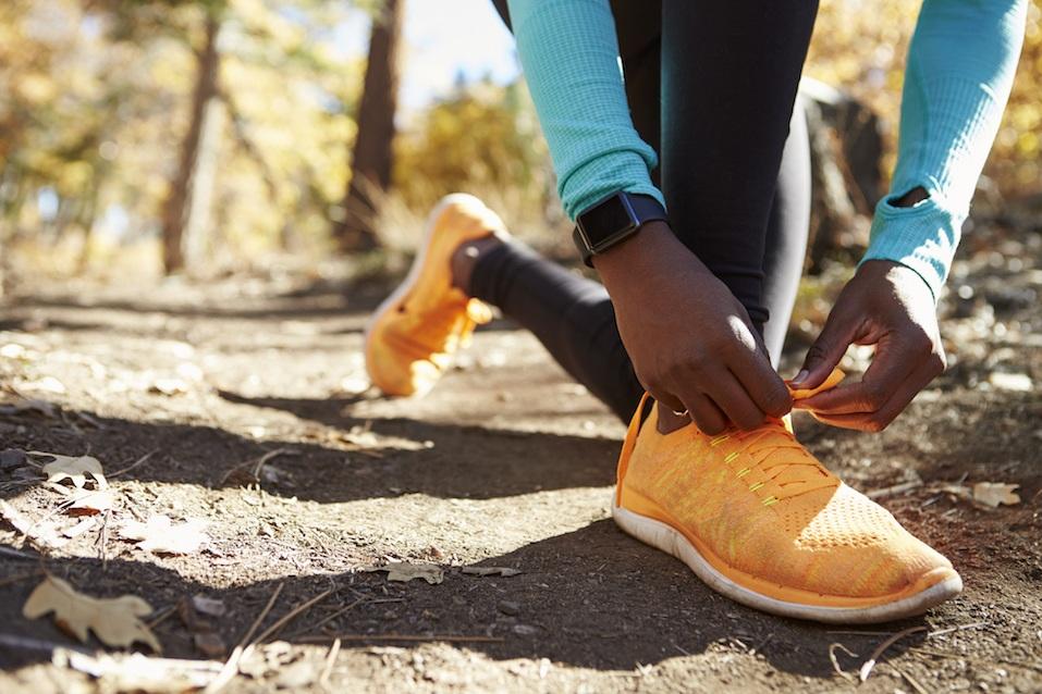 Black female runner in forest tying shoe