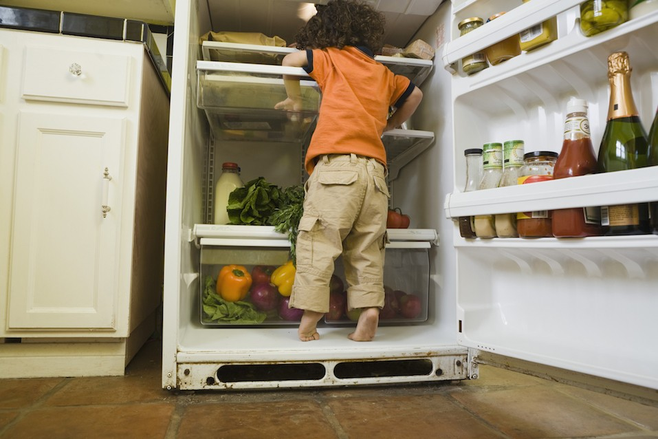 Boy standing in refrigerator looking for snack