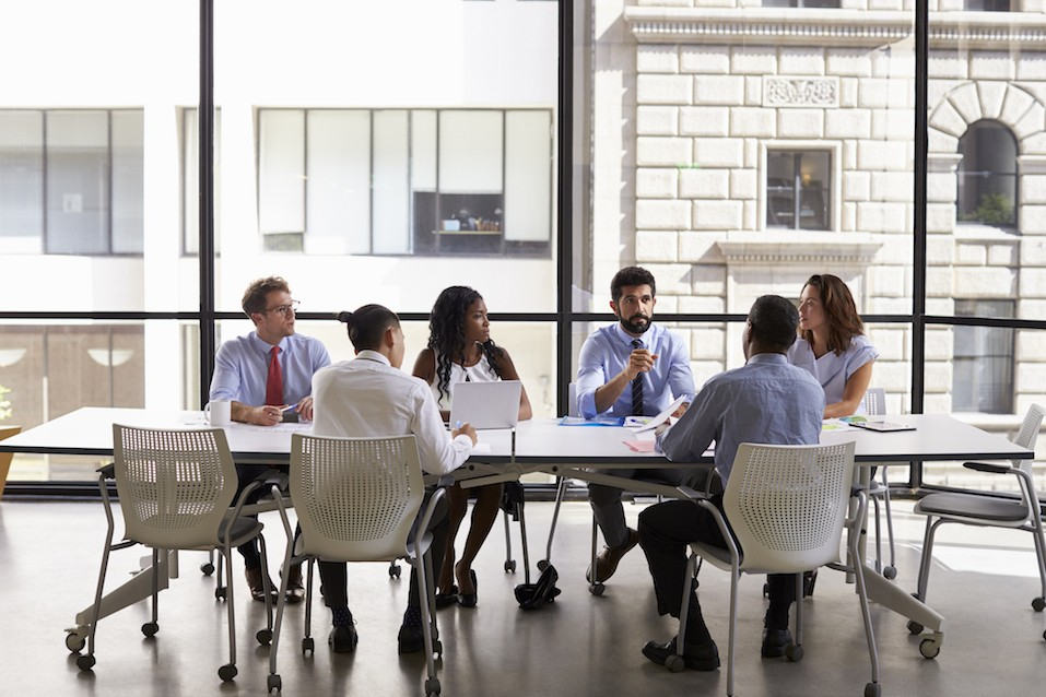 Business team look to manager at meeting in open plan