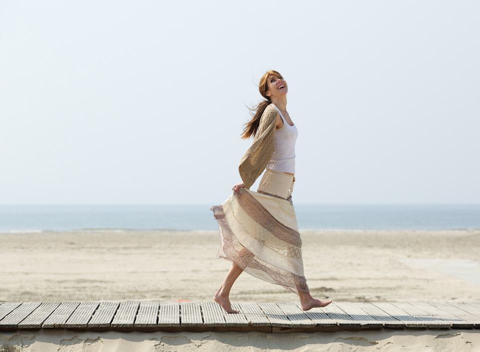 Carefree mature woman walking barefoot at beach