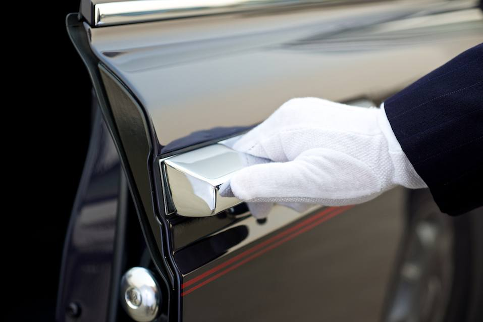 Chauffeur opens car door of a rolls royce