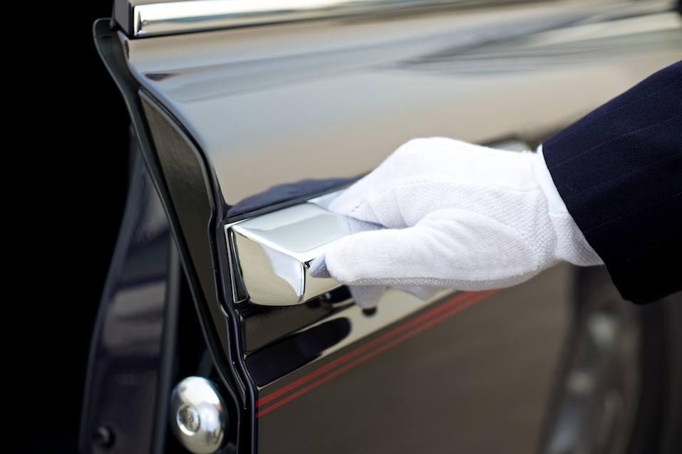 Chauffeur opens car door of a rolls royce