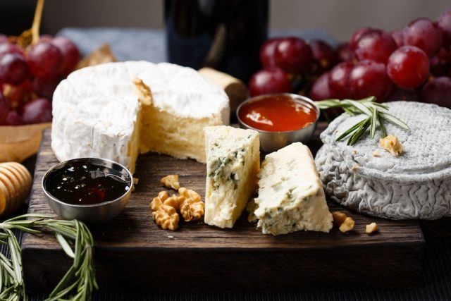 Cheese plate served with wine, jam, and honey