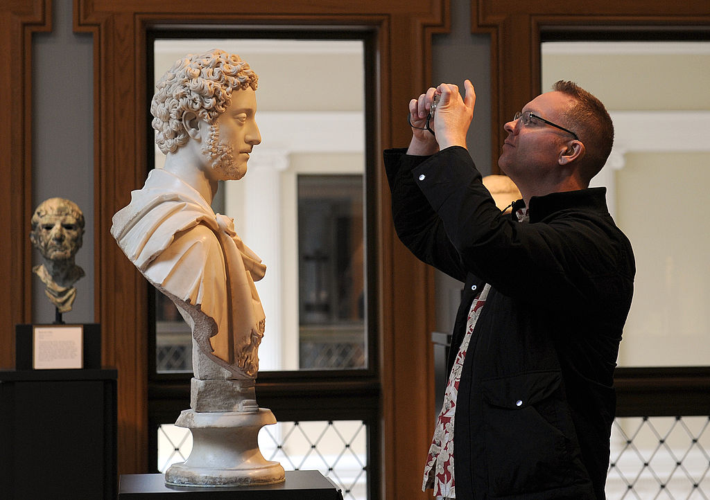 A visitor takes a picture of a bust of Roman Emperor Commodus.