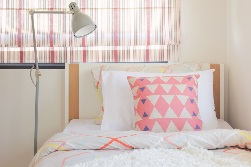 Coral pink triangle pattern pillow setting on bed with foldable reading lamp next to bed