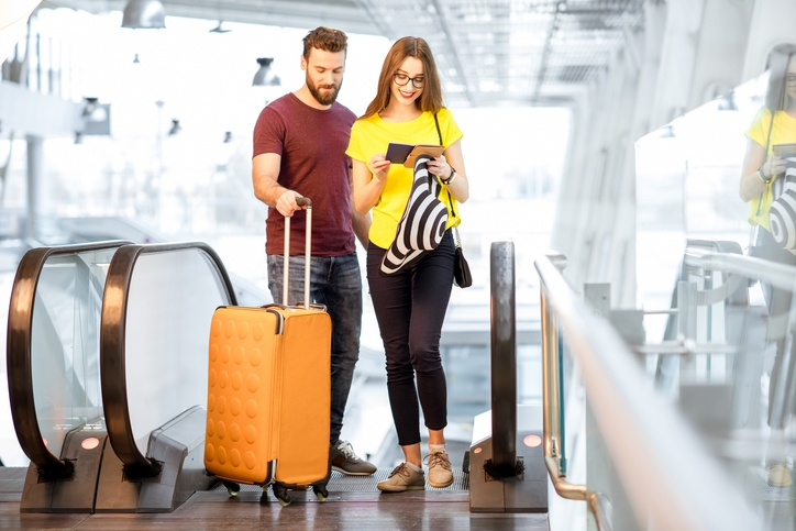 Young happy couple getting up with baggage on the escalator to the departure