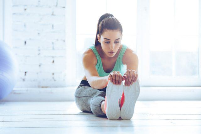 Woman in sportswear doing stretching while sitting on the floor.