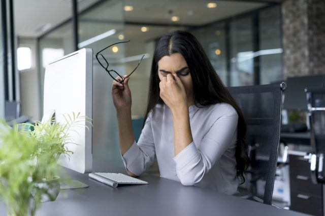 A depressed businesswoman rubbing her eyes in the office.