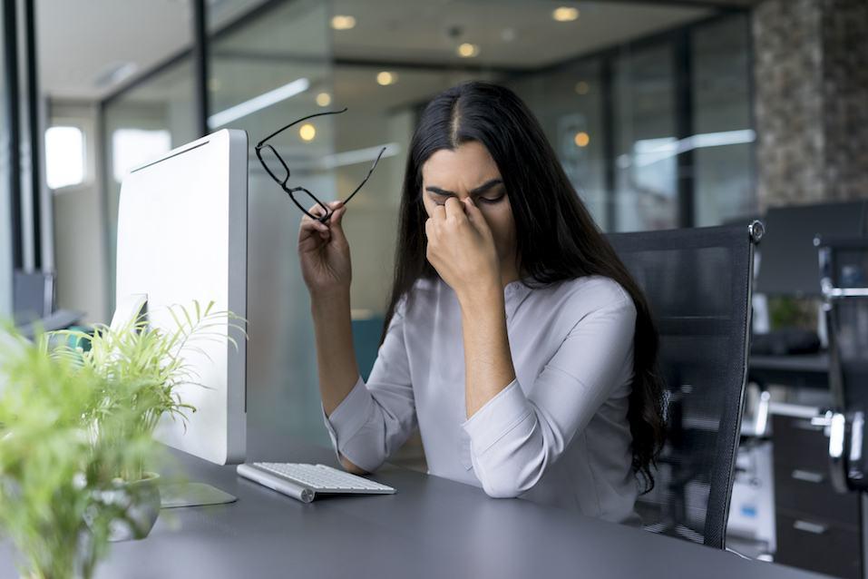Depressed businesswoman rubbing eyes in office