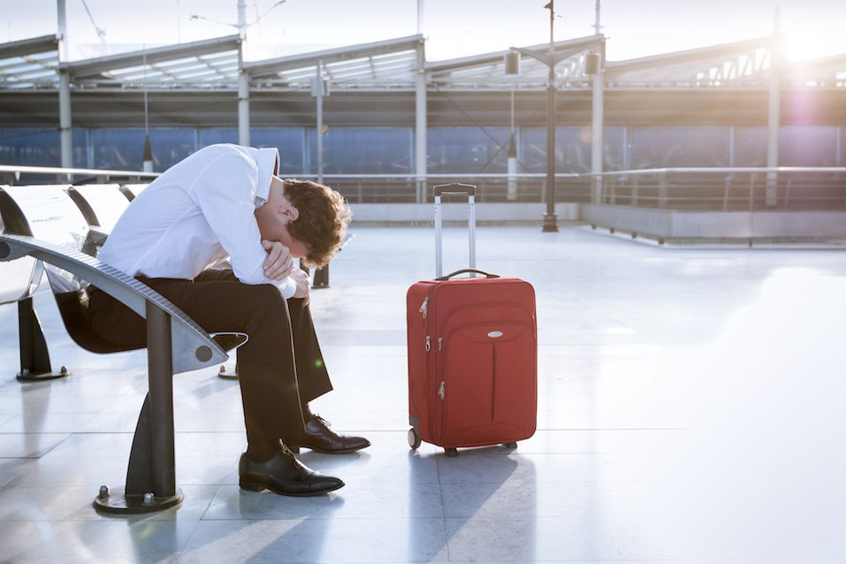 Depressed traveler waiting at airport, flights delays and cancellations