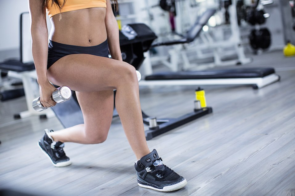 woman doing lunges with weights in a gym