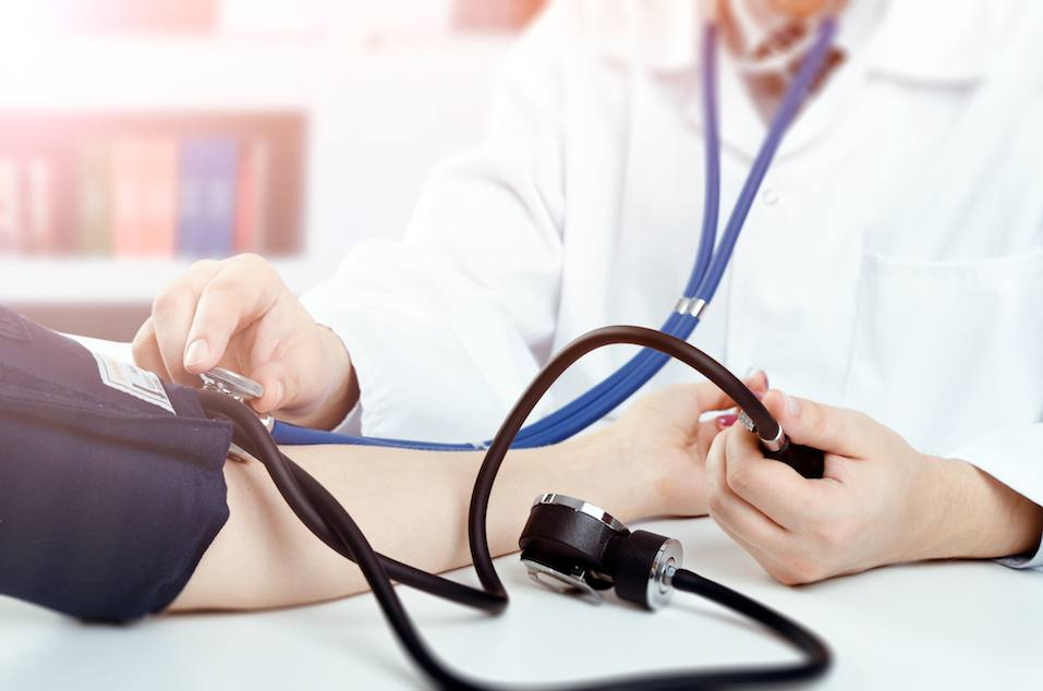 Doctor measures blood pressure of the patient