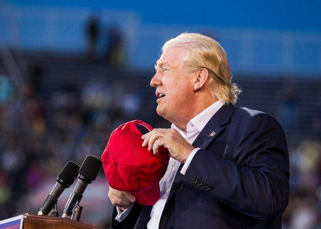 Donald Trump removes his hat while speaking in front of a podium.