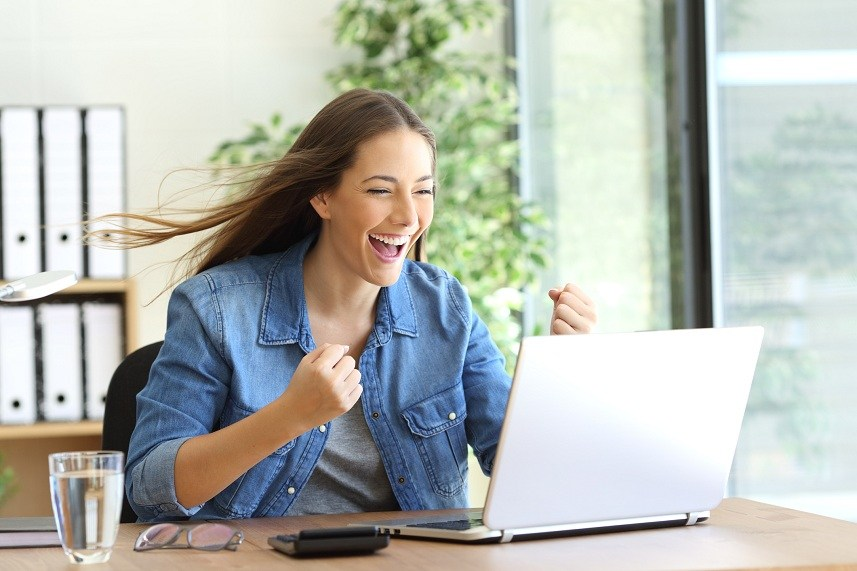 excited woman working on laptop
