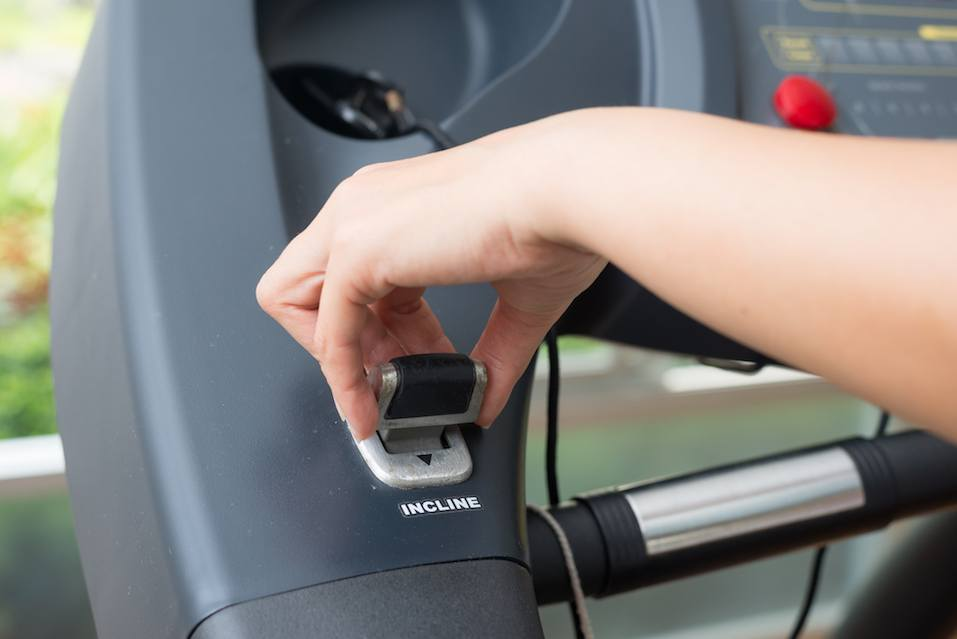 woman's hand adjustin incline stick on treadmill