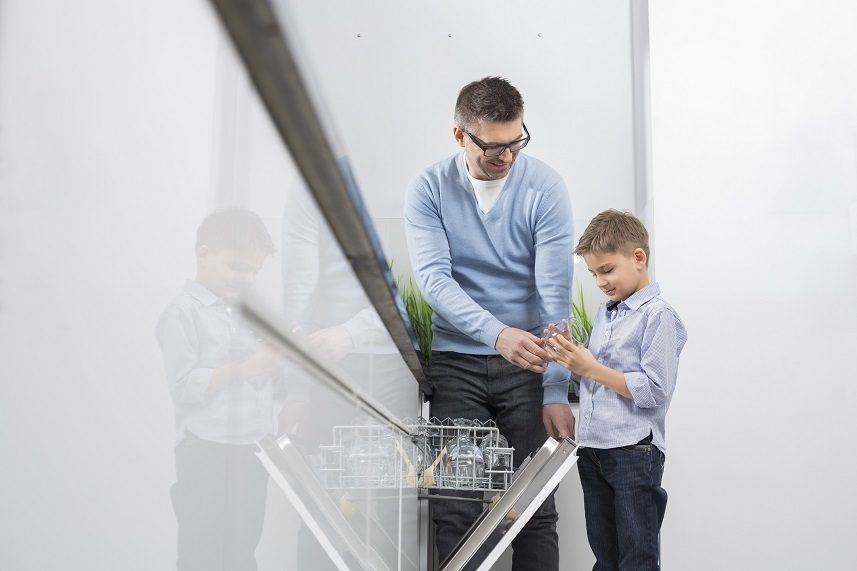 Father and son placing glass in dishwasher
