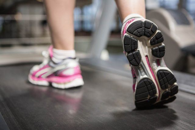 A woman's pink sneakers on a treadmill.