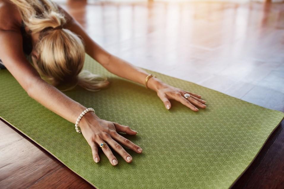 Woman doing balasana yoga at gym, with focus on hands.
