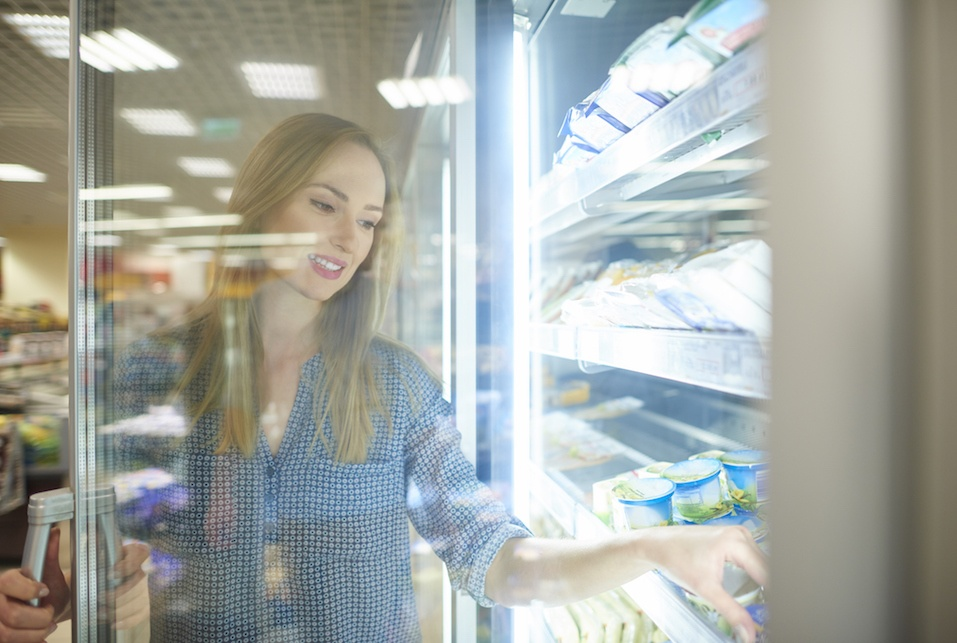 Female shopper reaching product from freezer