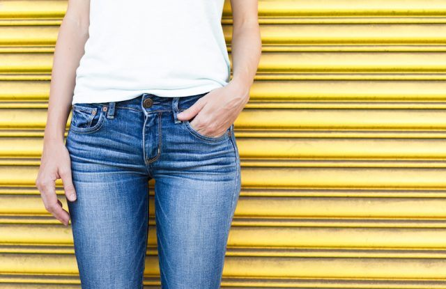 Female wearing jeans against a yellow background