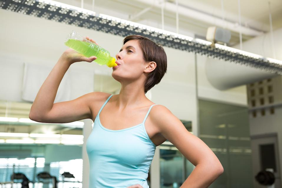 Fit brunette drinking energy drink at the gym