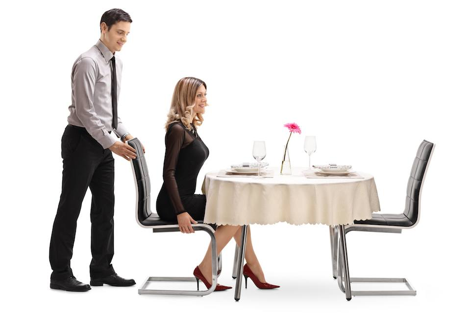 Gentleman helping his girlfriend with the chair