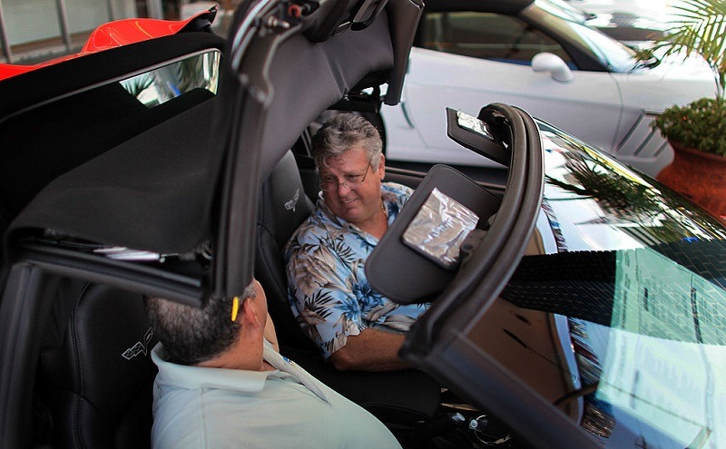 A car salesman talks to a customer while lowering the top of a convertible.