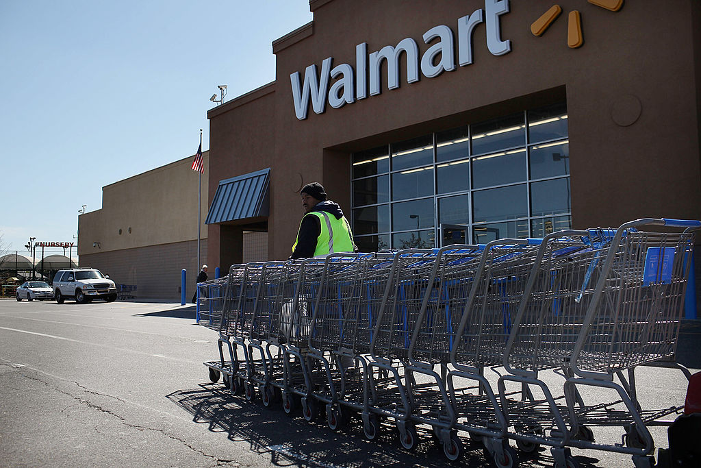 A man pushes carts to a corral