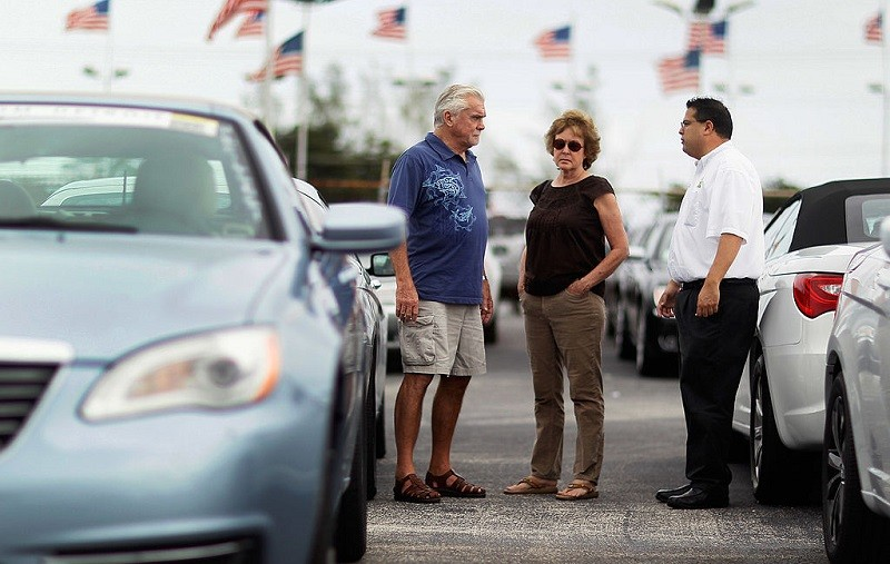 HOLLYWOOD, FL - OCTOBER 27: Salesman, JC Soto, (R) talks with customers, Paul Mulcahy and Sarah Even as they shop for a car on the sales lot of the Hollywood Chrysler Jeep dealership on October 27, 2011 in Hollywood, Florida. The sale of vehicles helped boost third quarter Gross domestic product (GDP), which grew at an inflation-adjusted annual rate of 2.5% from July through September, the strongest performance in a year.