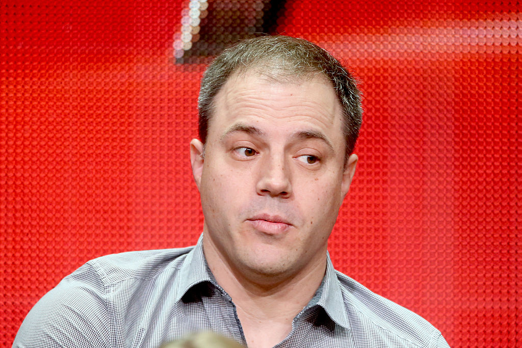 CCO at DC Geoff Johns looks to the side in front of a red backdrop
