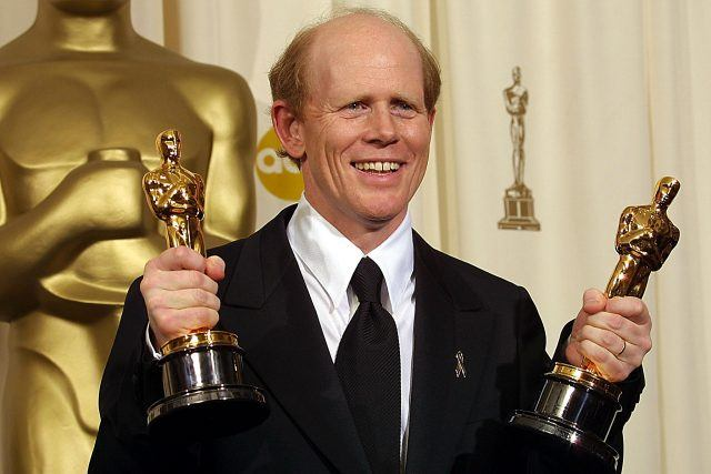 Ron Howard stands in a black suit and tie holding an Oscar award in each hand.