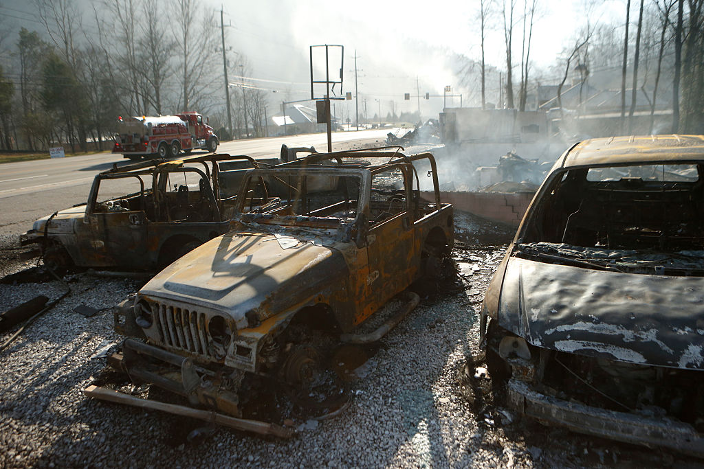 The remains of a Jeep rental business smolders after a wildfire in Gatlinburg, Tennessee