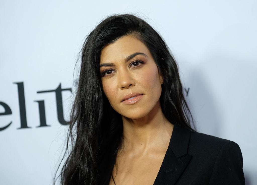Kourtney Kardashian poses in a black outfit