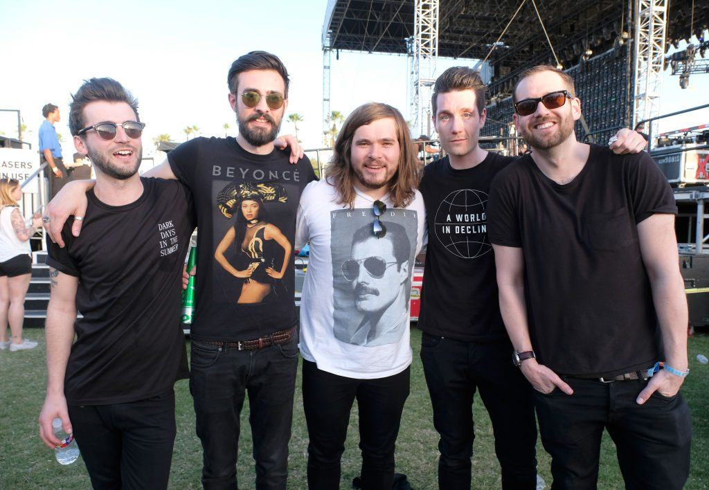 Members of the band Bastille pose with their arms around each other in front of a stage at Coachella