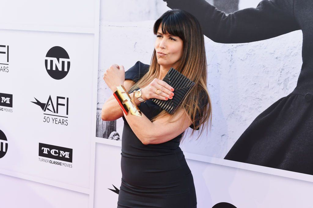 Patty Jenkins makes the Wonder Woman X with her arms on the red carper