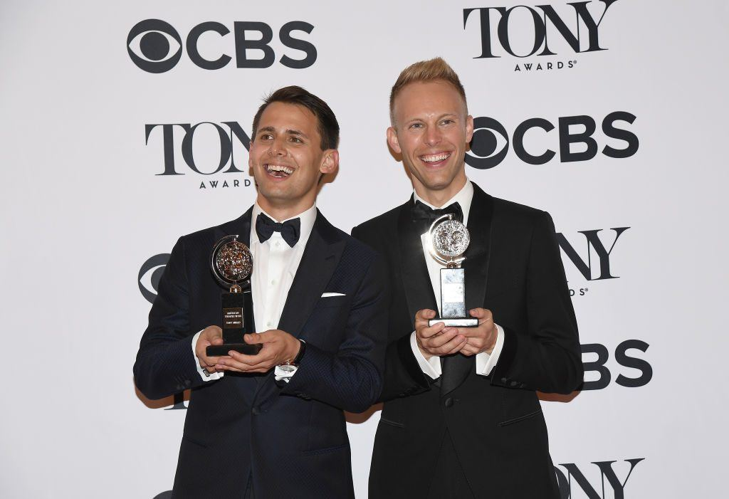 Benj Pasek and Justin Paul hold their awards in front of a sign for the Tony Awards