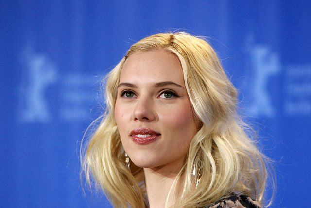 Scarlett Johansson smiles in front of a blue curtain.