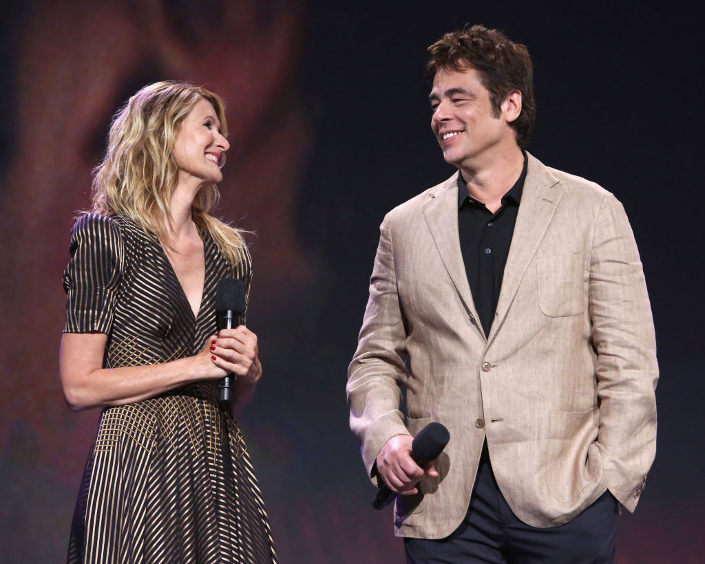 Laura Dern and Benicio del Toro smile at each other on stage