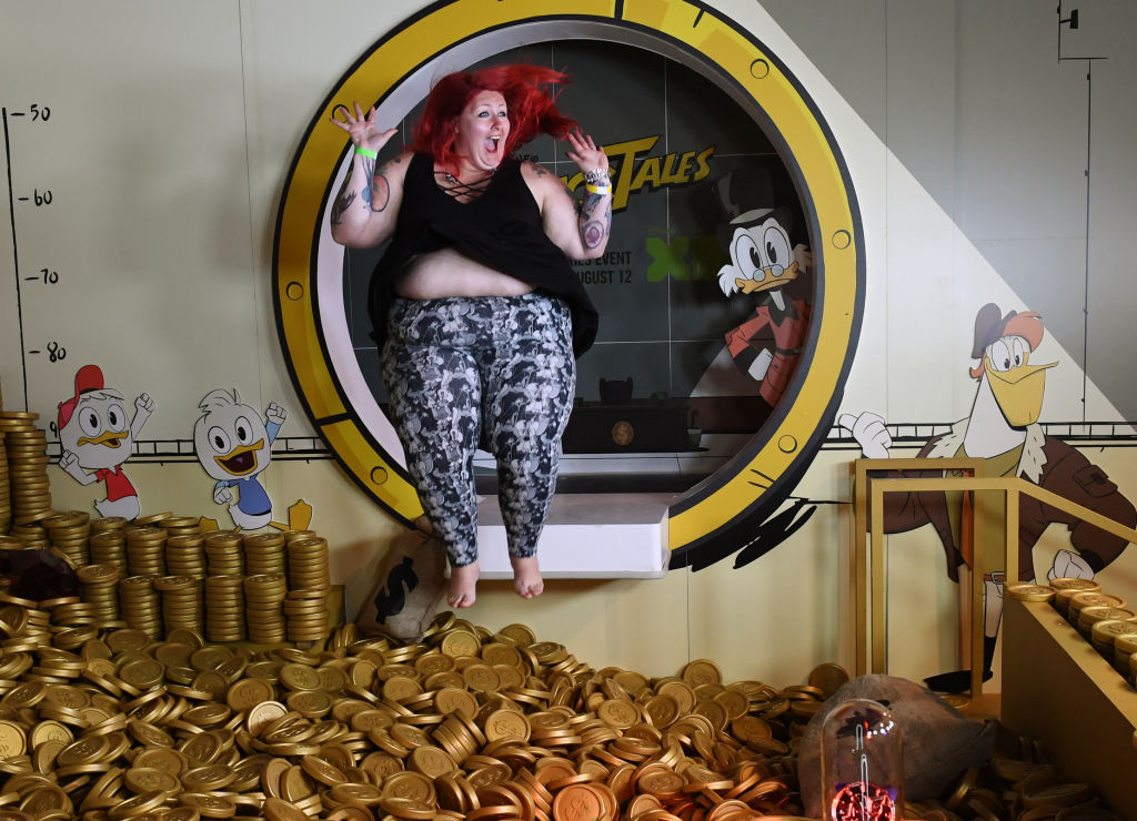 A woman jumps into the money pit at the Duck Tales exhibit
