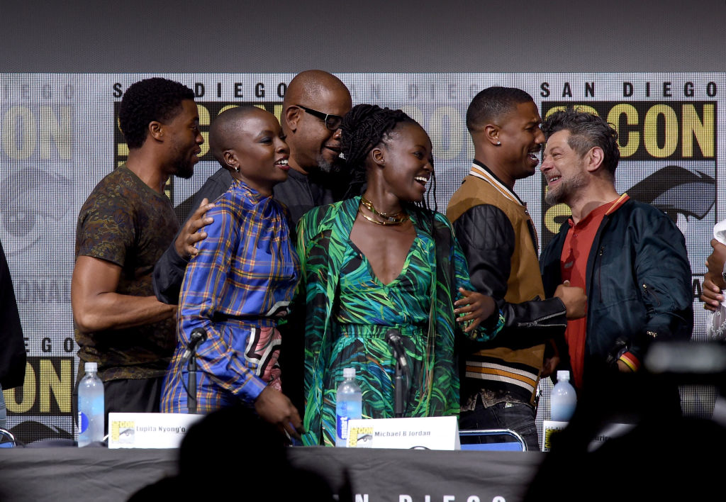 Black Panther cast members smiling and embracing on stage at Comic-Con
