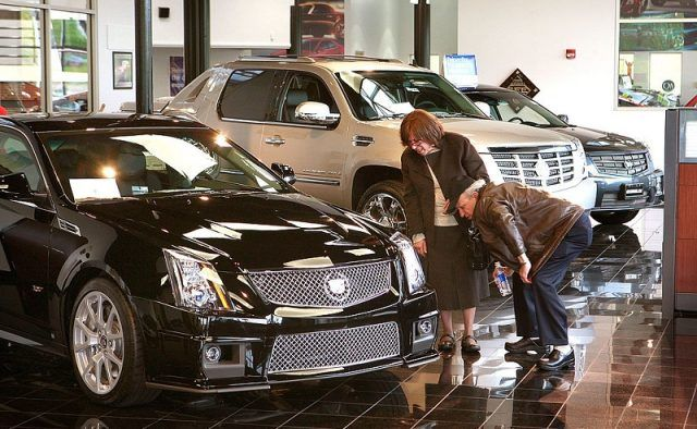 Customers look over Cadillacs offered for sale at a GM dealership